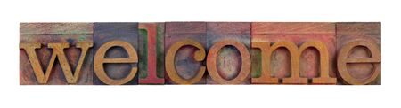 the word welcome in vintage wood letterpress type blocks, stained by color ink, isolated on white Stock Photo - 7224438
