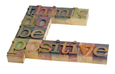 letterpress type: think, do, be positive - motivational slogan in vintage wooden letterpress type blocks, stained by color ink, isolated on white