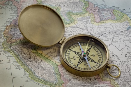 vintage pocket brass compass over old map of South America published in 1926 (expired copyrights)