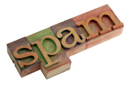 unsolicited: the word spam (unsolicited and unwanted commercial email messages) - vintage wooden letterpress type blocks, stained by color ink, isolated on white
