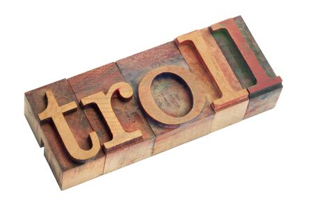 letterpress  type: the word troll (a creature from Nordic mythology or someone who posts inflammatory or off-topic messages in online community) - vintage wooden letterpress type blocks, stained by color ink, isolated on white