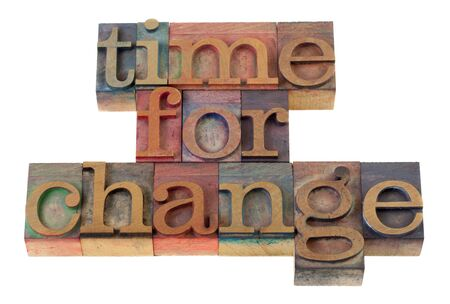 time for change headline words in vintage wooden letterpress type blocks, stained by color ink, isolated on white