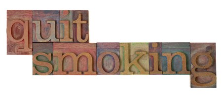 quit smoking words in vintage wooden letterpress type blocks, stained by color ink, isolated on white Stock Photo