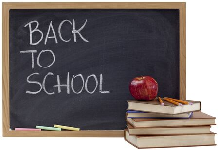 back to school concept - white chalk handwriting on blackboard, stack of old books, red apple and yellow pecils
