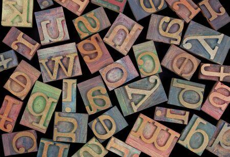 letters of alphabet in vintage wood letterpress printing blocks, placed randomly on black background photo