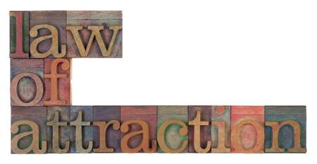 law of attraction words in vintage wooden letterpress printing blocks, stained by color inks, isolated on white 版權商用圖片