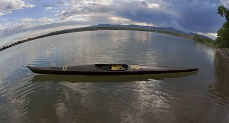 skiny: fisheye lens perspective - long and skiny racing kayak on a calm lake with Rocky Mountains. Temporary number 13 on deck added by the photographer.