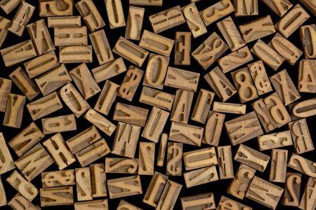 background of randomly placed wooden letterpress printing blocks, black background photo