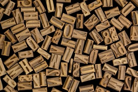background of randomly placed wooden letterpress printing blocks, black background Фото со стока