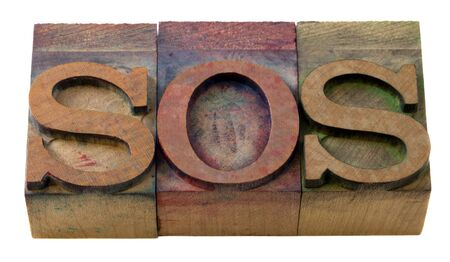 call for help - SOS word in vintage wooden letterpress printing blocks, isolated on white Stock Photo - 7543893