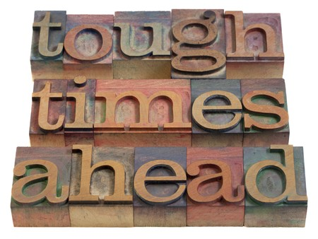 tough times: tough times ahead warning - vintage wooden letterpress printing blocks, stained by color inks, isolated on white Stock Photo