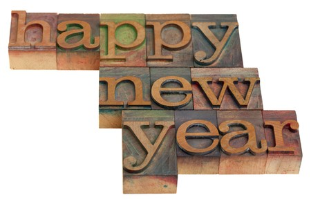 letterpress words: Happy New Year greetings in vintage wooden letterpress printing blocks, isolated on white