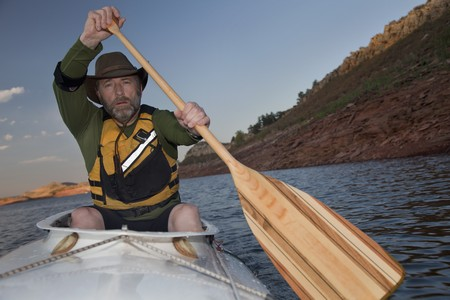 horsetooth reservoir: mature male paddling a white decked expedition canoe with wooden paddle on mountain lake with red sandstone cliffs (Horsetooth Reservoir near Fort Collins, Colorado)