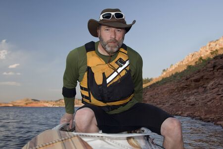 horsetooth reservoir: mature male boarding his canoe on a mountain lake with red sandstone cliffs (Horsetooth Reservoir near Fort Collins, Colorado)