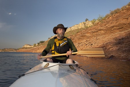 horsetooth rock: mature adult paddler in an expedition decked canoe on calm mountain lake (Horsetooth Reservoir near Fort Collins, Colorado)
