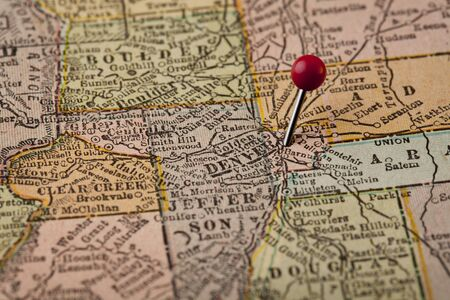 map pin: Denver on vintage 1920s map of Colorado with a red pushpin, selective focus