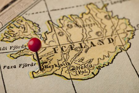 Iceland on vintage 1920s map with a red pushpin on Reykjavik, selective focus photo