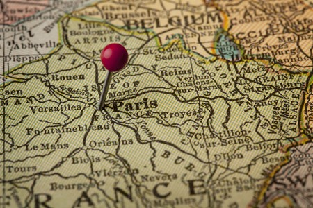 Paris on vintage 1920s map of France with a red pushpin, selective focus