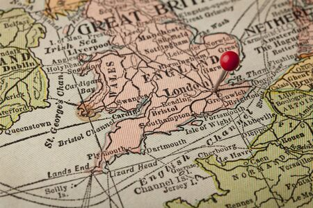 map pin: England and ENglish CHannel vintage 1920s map (printed in 1926 - copyrights expired) with a red pushpin on London, selective focus