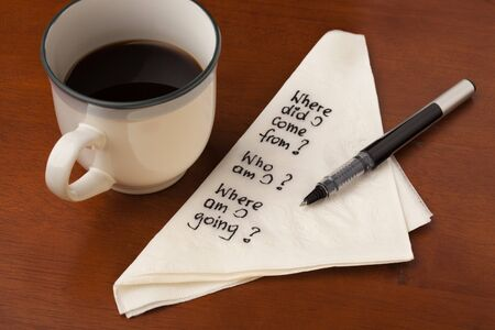 am: Who am I and other spiritual life questions - handwrting on napkin with coffee cup on wooden table