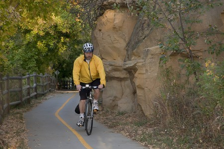 poudre river: middle aged male riding a bike or commuting on biking trail, Poudre River Corridor Trail near Greeley, Colorado, fall scenery