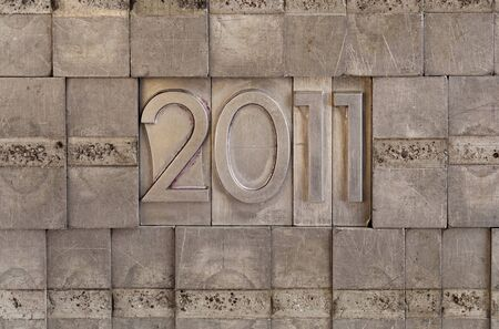 New Year of 2011 - numbers in vintage scratched metal letterpress printing blocks, wall background Stock Photo - 7912049
