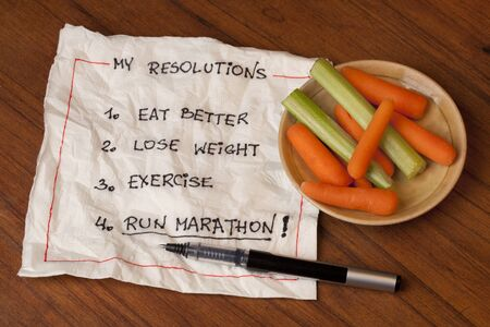 healthy and ambitious  New Year resolutions (diet, lose weight, exercise, run marathon) - napkin handwriting with baby carrot and celery snaks on wooden table