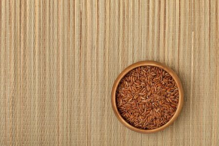 a small wooden bowl of brown rice on a grass mat Stock Photo - 7978968