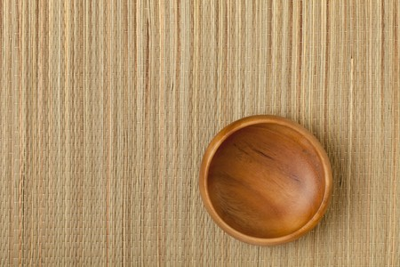 a small empty wooden bowl on grass mat Stock Photo - 7978970