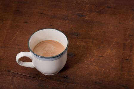 white porcelain cup of coffee with cream on old, scratched and cracked wooden table Stock Photo - 7978963