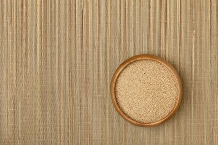 a small wooden bowl of amaranth grain on a grass mat Stock Photo - 7978973