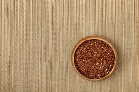 a small wooden bowl of red quinoa grain on a grass mat Stock Photo - 7978974