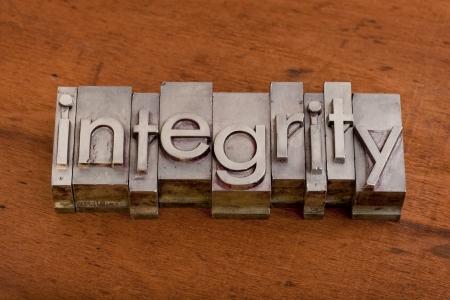 integridad: palabra de integridad en tipograf�a vintage, metal, impresi�n de bloques en fondo rayado de madera Foto de archivo