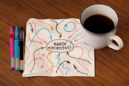 brainstorming concept - arrows representing ideas, inputs and feedbacks sketch on a napkin with a cup of coffee on table Stock Photo - 8031163
