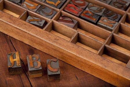 A, B and C letters in vintage wooden letterpress type (Abbey typeface) with old typesetter case in background, image can be flipped in horizontal for original view of printing blocks Stock Photo - 8096095