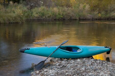 blue whitewater kayak on a rocky shore against river with gold color reflection Stock Photo - 8096094