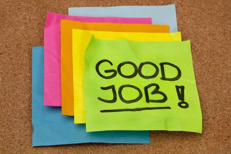good job: good job - congratulation, a stack of colorful sticky notes on cork bulletin board
