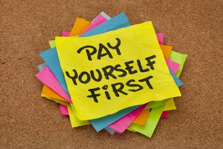 pay yourself first, a reminder of personal finance strategy - stack of colorful sticky notes on a cork bulletin board