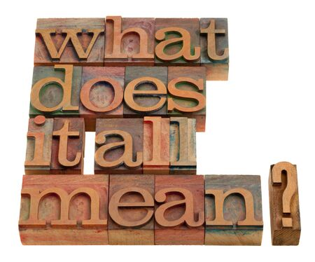 what: what does it all mean - spiritual and philosophical question in vintage wooden letterpress prinitng blocks isolated on white Stock Photo