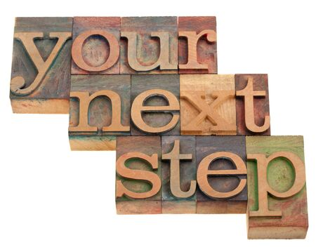 your next step - phrase in vintage wooden letterpress printing blocks isolated on white