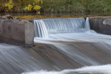 detail of old river dam diverting water for farmland irrigation, Cache la Poudre RIver in Fort Collins, Colorado, fall scenery Фото со стока