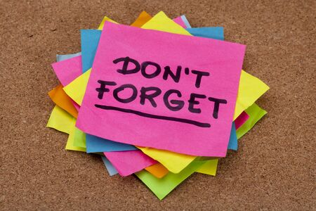 not to forget: do not forget reminder - a stack of colorful sticky notes on cork bulletin board