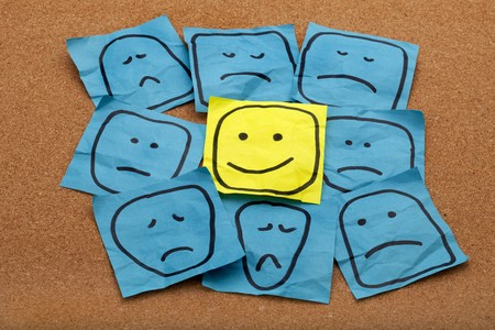 POSITIVE NEGATIVE: positive attitude or optimism concept - happy smiley face on yellow sticky note surrounded by sad unhappy blue faces