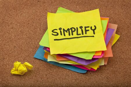 pragmatic or get organized concept, simplify reminder - a stack of colorful sticky notes on cork bulletin board Stock Photo