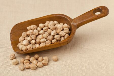 chickpea (garbanzo bean) on a rustic, wooden scoop against tablecloth Stock Photo - 8096117