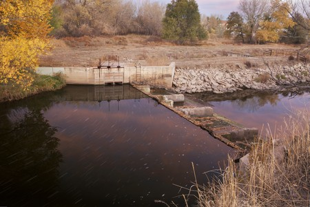 diversion dam with water flowing into irrigation ditch inlet, Cache la Poudre River at Fort Collins, Colorado, fall scenery at dawn Stock Photo - 8178671