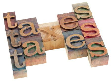 taxes word abstract in vintage wooden letterpress printing blocks isolated on white Stock Photo - 8178678
