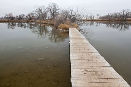 nature trail - boardwalk pathway over lake in old gravel quarry converted into park (Riverbend Ponds in Fort Collins, Colorado), late fall nostalgic scenery Stock Photo - 8265003