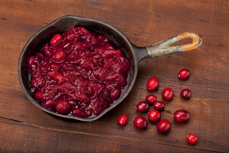 freshly fried cranberry sacuce on a small iron pan and some fresh berries against old scratched wooden table top Stock Photo - 8265008