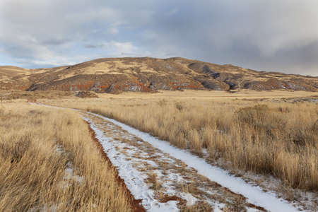 hiking trail on a ranch road with snow and footprints - Red Mountain Open Space in northern Colorado (Larimer County), fall scenery with dry grass photo